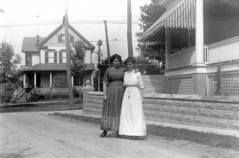 Two women standing on Dearr Street in East Stroudsburg with their backs to the Sam Scott house at 152 N. Courtland St., circa 1912.