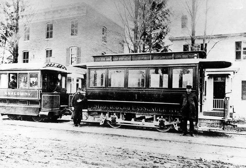 "Two trolley cars running along Main Street in Stroudsburg. First trolley car (to the right) is for ""Stroudsburg Passengers."" The second is for ""Analomink."""